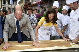 Andreas Goebes of the bakers guild Heidelberg, right, watches as Britain's Prince William, left, and Princess Kate, form dough into pretzels during their visit of the market in the historic center of the German city of Heidelberg, July 20, 2017.