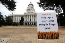 FILE - A sign alerts visitors to water conservation efforts at the state Capitol in Sacramento, Calif., July 8, 2014. On Friday, California Gov. Jerry Brown declared an end to the state's water emergency following a five-year drought.