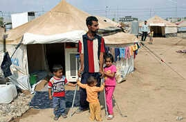 Syrian refugees stand near their tent at Kawergost refugee camp in Irbil, 217 miles (350 kilometers) north of Baghdad, Iraq, Sept. 22, 2013.