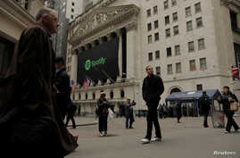 Pedestrians walk past a banner with the Spotify logo on it as the company lists its stock on the New York Stock Exchange with a direct listing in New York, April 3, 2018.