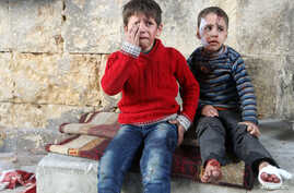 Injured boys react at a field hospital after airstrikes on the rebel held areas of Aleppo, Syria, Nov. 18, 2016.