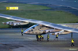 Crew members push the solar-powered plane Solar Impulse 2 to its parking position at Nagoya airport after changing weather conditions thwarted a planned take-off, June 24, 2015.