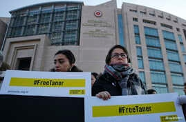 Human rights activists stage a protest outside a court in Istanbul, Wednesday, Jan. 31, 2018, where the trial of eleven human rights activists accused of belonging to and aiding terror groups was held. While the eleven were recently released, Amnesty