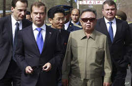 North Korean leader Kim Jong Il, second right, and Russian President Dmitry Medvedev, second left, walk during a meeting an a military garrison, outside Ulan-Ude, August 24, 2011