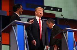 Republican presidential candidates, from left, Scott Walker, Donald Trump, and Jeb Bush are seen during a break at the first Republican presidential debate at the Quicken Loans Arena, Aug. 6, 2015, in Cleveland.