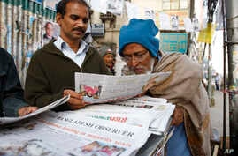 FILE - People catch up with news at a newspaper stall in Dhaka, Bangladesh.