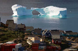 FILE - An iceberg floats near a harbor in the town of Kulusuk, Greenland.