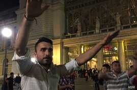 A Syrian man organizes a sit-in outside Budapest's East railway station Friday night as thousands of stranded migrants await passage to Austria, and ultimately Germany, Sept. 4, 2014 (VOA / L. Ramirez).