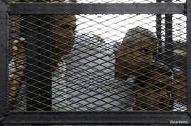 From left, Peter Greste, Mohamed Fahmy and Baher Mohamed listen to the ruling at a court in Cairo, Egypt, June 23, 2014.