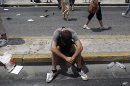 A protester sits on the road in front of the Greek Parliament during a protest  in Athens, Tuesday, July 16, 2013. Unions opposing austerity measures in Greece staged their fourth general strike this year on Tuesday, as the government prepared to sta