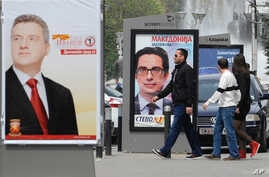 """Young people pass beside boards with election posters of Gjorge Ivanov, left, current Macedonian President and a candidate of the ruling conservative VMRO-DPMNE party, with a slogan """"The State Before All"""", and Stevo Pendarovski, center, a candidate o"""