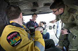 Prime Minister Justin Trudeau, center, prepares to fly over devastation from a wildfire during a visit to Fort McMurray, Alberta, Canada, May 13, 2016.
