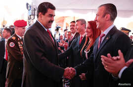 Venezuela's President Nicolas Maduro, center, shakes hands with Venezuela's new vice president Tarek El Aissami during a meeting with ministers in Caracas, Jan. 4, 2017.