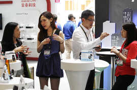 Vendors explain their products on the opening day of the Computex exhibition at the Taipei World Trade Center in Taipei, Taiwan, June 5, 2012.