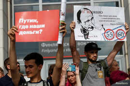 Protesters hold posters during a rally against planned increases to the nationwide pension age in St. Petersburg, Russia, Sept. 9, 2018.