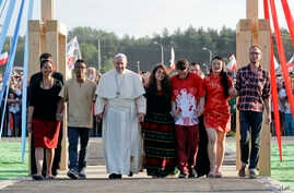 Pope Francis, accompanied by youths, passes through the Door of Mercy ahead of a prayer vigil on the occasion of the World Youth Days, in Campus Misericordiae in Brzegi, near Krakow, Poland, July 30, 2016.