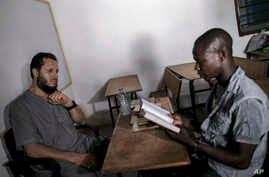 In this photo taken Saturday, March.18, 2017, Abdul Ghani Bandenjki, left, teaches Arabic and the Quran, in a School in Tema, Ghana.