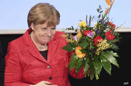 German Chancellor Angela Merkel holds a bouquet of flowers at a convention of the Christian Democrats' branch in northeastern Mecklenburg-Western Pomerania state in Stralsund, Germany, Feb. 25, 2017.