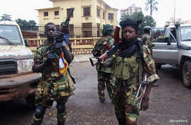 Fighters for the Seleka rebel alliance stand guard in front of the presidential palace in Bangui, Central African Republic, March 25, 2013.