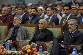 FILE - Afghan President Ashraf Ghani, center, former President Hamid Karzai, left, and Afghan chief executive Abdullah Abdullah, right, attend during a ceremony marking the first anniversary of the death of Former Afghan Vice President Marshal Mohamm