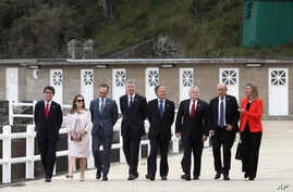 Participants of a G-7 ministerial meeting walk to have a group photo taken on the second day of their talks, in Dinard, France, April 6, 2019.