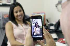 FILE - Lauren Simo (L) answers questions during a weekly forum streamed via Periscope on a smartphone, Hollywood, Fla., 29, 2015.
