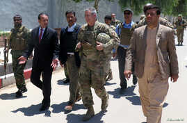 U.S. Army General John Nicholson, commander of Resolute Support forces and U.S. forces in Afghanistan, center, walks with Afghan officials during an official visit in Farah province, Afghanistan, May 19, 2018. Picture taken May 19, 2018.