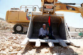 A man holding a Palestinian flag protests as he sits in the scoop of an Israeli excavator as tries to prevent it from clearing his land during a protest against Jewish settlements, near the village of Deir Qaddis near the West Bank city of Ramallah J