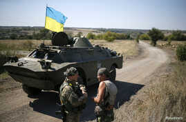 Ukrainian servicemen speak near an armored vehicle in their camp near Donetsk Sept. 2, 2014.