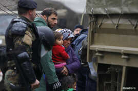Macedonian soldiers escort migrants who have crossed the border illegally from Greece, into army trucks in the village of Moini, Macedonia, March 14, 2016.