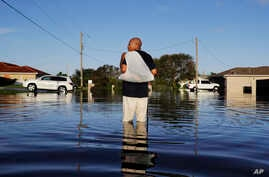 A man walks through a flooded street from Hurricane Irma after retrieving his uniform from his house to return to work at a supermarket in Fort Myers, Florida, Sept. 12, 2017.