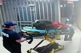 In this July 13, 2015, frame taken from video provided by the Waller County Sheriff's Department from a motion-operated camera, emergency personnel  carry a gurney near Sandra Bland's jail cell, at the Waller County jail in Hempstead, Texas.