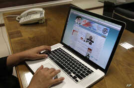 FILE - An Iranian checks the newly launched website of Iran's Intelligence Ministry, in Tehran, Iran, Oct. 10, 2012. A glimpse into the shadow world of Iran's main spy agency is now a click away. The Intelligence Ministry now hosts a website with add