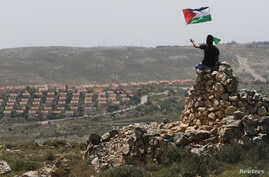 A protester waves a Palestinian flag in front of the Jewish settlement of Ofra during clashes near the West Bank village of Deir Jarir near Ramallah Apr. 26, 2013.
