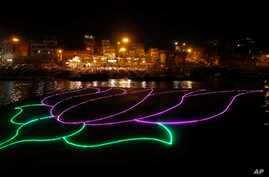 An illumination in the shape of a lotus, party symbol of the winning Bharatiya Janata Party, illuminates the River Ganges in Varanasi, in the northern Indian state of Uttar Pradesh, May 16, 2014.