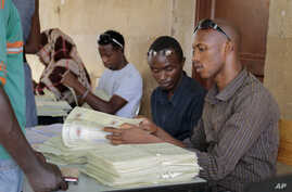 FILE - A new Burundi electoral schedule has been proposed for a July 15 presidential election. Here, election workers distribute voter cards in the capital, Bujumbura, June 4, 2015.