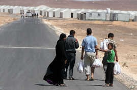 A Syrian refugee family walks towards the new Syrian camp of Azraq, which stretches for 15 kilometers, and lies about 100 kilometers from the Syrian border in Jordan, Wednesday, April 30, 2014.
