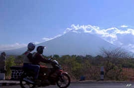 Motorists ride past Mount Agung volcano, seen in the background, in Karangasem, Bali, Indonesia, Sept. 28, 2017. Warnings that the volcano on the tourist island will erupt have sparked an exodus as authorities have ordered the evacuation of villagers