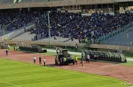 """In this photo shared on social media, an Iranian military vehicle is deployed at Tehran's Azadi Stadium on August 10, 2018 in an apparent effort to quiet football fans chanting """"death to the dictator"""" ahead of a match."""