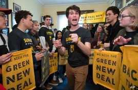 Jeremy Ornstein of Watertown, Mass., center, cheers on fellow environmental activists as they occupy the office of Rep. Steny Hoyer, D-Md., the incoming majority leader on Capitol Hill in Washington, Dec. 10, 2018.