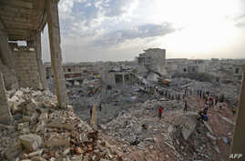 Syrians gather amidst destruction in Zardana, in the mostly rebel-held northern Syrian Idlib province, in the aftermath of air strikes in the area late on June 8, 2018.