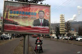 "FILE - A billboard shows Chinese President Xi Jinping with the slogan ""To exactly solve the problem of corruption, we must hit both flies and tigers,"" in Gujiao, in northern China's Shanxi province, Feb. 6, 2015."