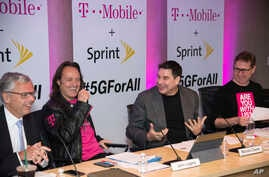 T-Mobile and Sprint executives enjoy a laugh as they accounce the two companies' planned merger April 29, 2018, in New York.