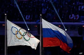 FILE - In this Feb. 23, 2014, photo, the Russian national flag, right, flies next to the Olympic flag during the closing ceremony of the 2014 Winter Olympics in Sochi, Russia.