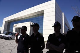 Police officers are seen outside the premises of Koza Ipek Holding, a media group close to U.S.-based moderate Islamic cleric Fethullah Gulen, in Ankara, Turkey, Sept. 1, 2015.