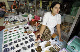 FILE - A woman from Myanmar sells rubies and other semi-precious stones at a market in Mae Sot, Thailand, Oct. 21, 2007. A U.S. a ban on the import of jadeite and rubies, one of Myanmar's most profitable industries, remains in place.
