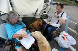 Evacuees Donna Herzog and her husband Richard Herzog, with their five dogs, eat food served by volunteers, in the aftermath of Tropical Storm Harvey, in a staging area as they wait for buses to go to evacuation shelters in Vidor, Texas, Sept. 1, 2017