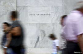 People walk past the Bank of Greece in Athens, June 19, 2015.