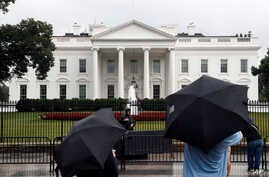 People stand on Pennsylvania Avenue as rain falls at the White House, July 28, 2017, in Washington. Rarely has the gap between the priorities of a president and lawmakers in his own party been so stark in the nation's capital.