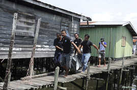 Villagers carry the body of a dead gunmen that was killed on Saturday, Simunul village in Sabah's Semporna district, March 4, 2013.
